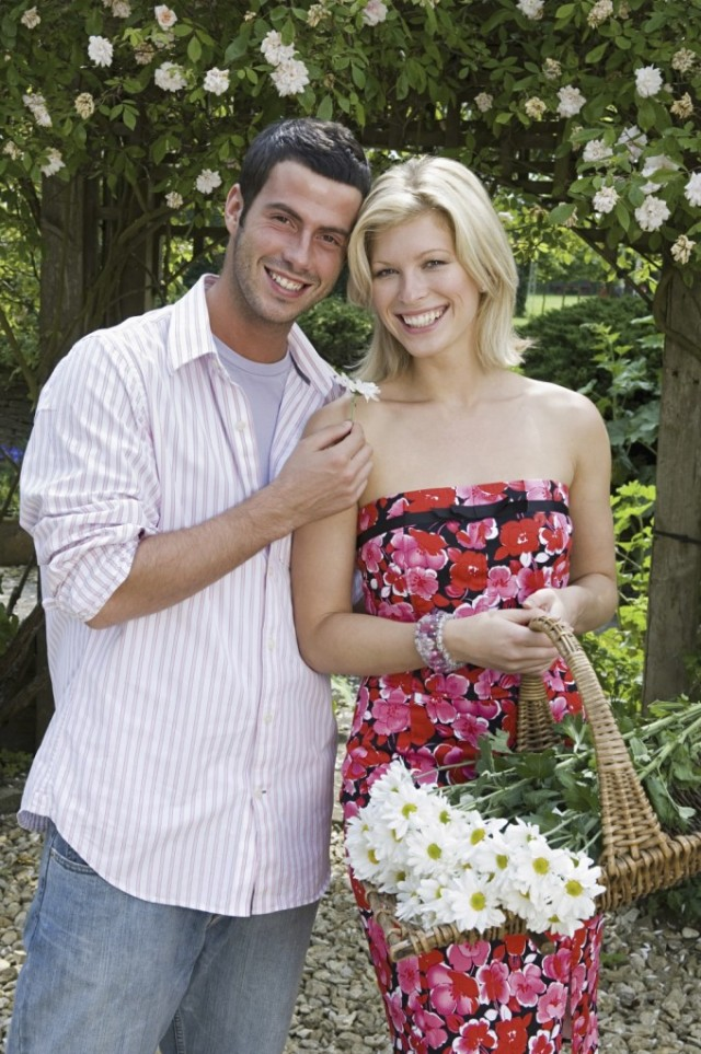 Two people, a smiling couple, in a garden