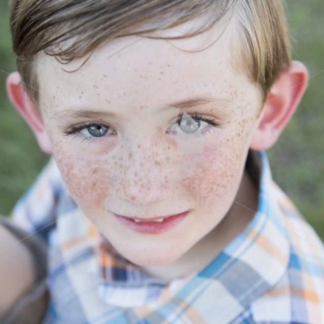 Portrait of a young boy with blue eyes and freckles on his nose