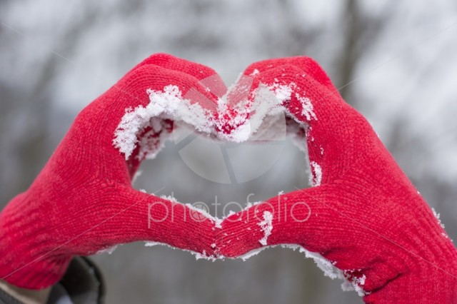 Red woolen glooves making a heart shape in snow