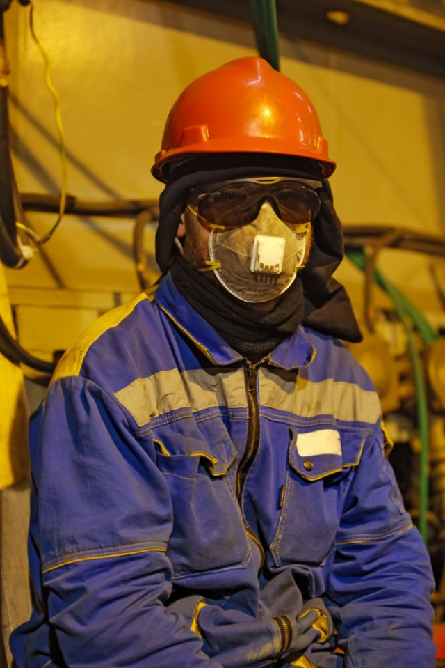 The worker in overalls and a respirator