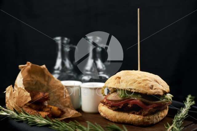 Craft beef burger and baked potatoes in a country style on wooden table on dark blue background.