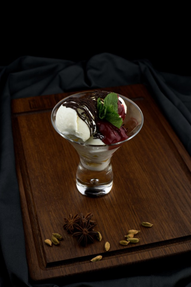 Vanilla ice cream in a glass on a dark background.