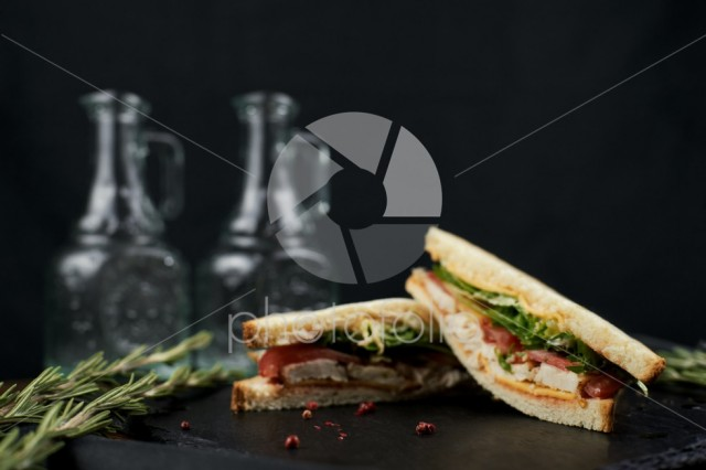 Sandwich with chicken, herbs and tomatoes on a dark background.