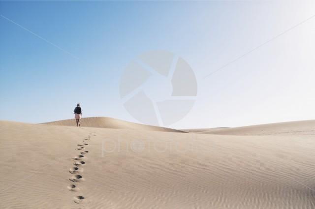Woman walking along a desert in Arizona, USA.