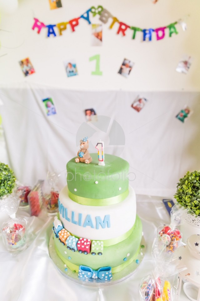 Green And White Birthday Cake With One Year Old Candle