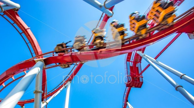 Yellow roller coaster with people inside move fast, high speed