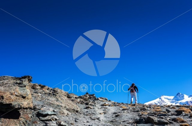 Female with her backpack trek on high Alps mountain in summer