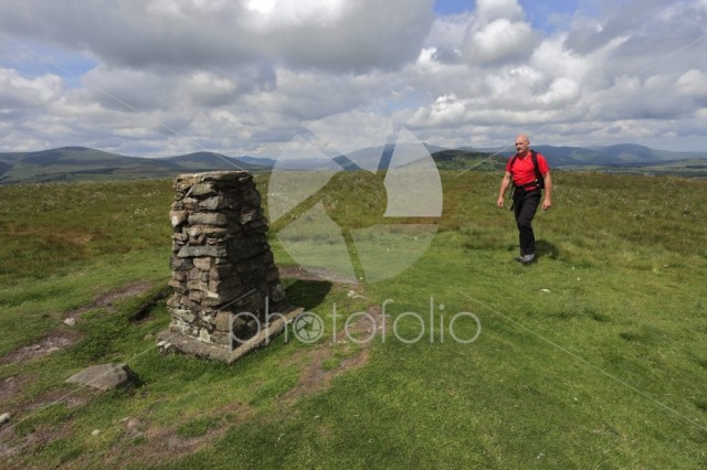 Walker at the Ordnance survey trig point, summit of Little Mell