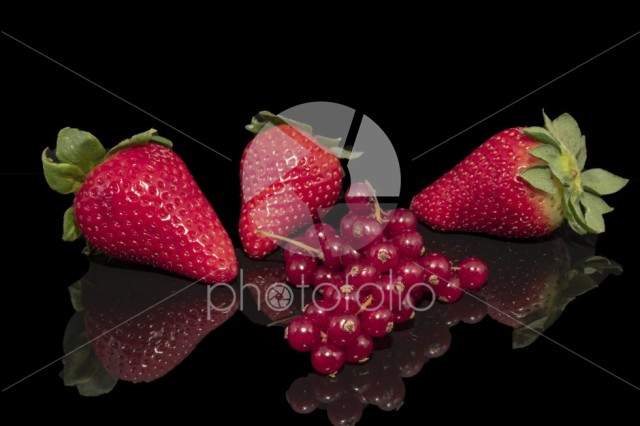 Strawberries and currant on a reflective surface
