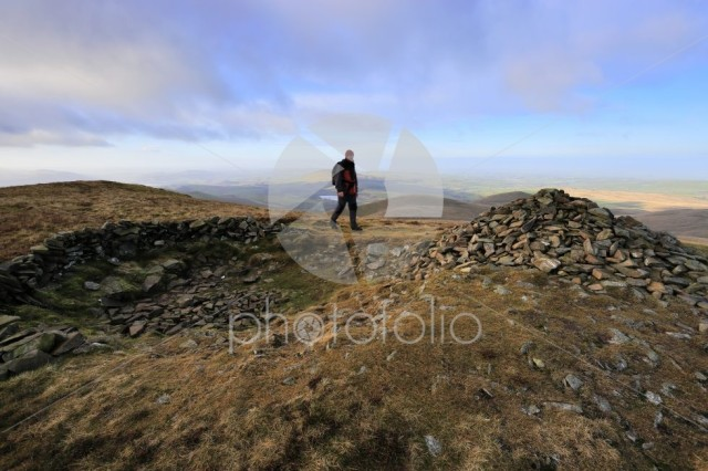 Walker at the Summit cairn on Little Sca fell, Uldale Fells