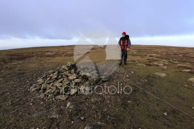 Walker at the Summit cairn on Knott fell, Uldale Fells
