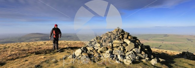 Walker at the Summit cairn on Brae fell, Lake District