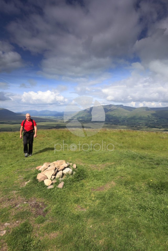 Walker at the summit of Great Mell Fell, Lake District