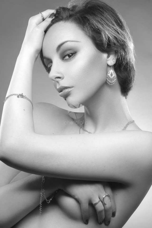 Black and white beauty studio portrait of a young exotic topless woman wearing jewels