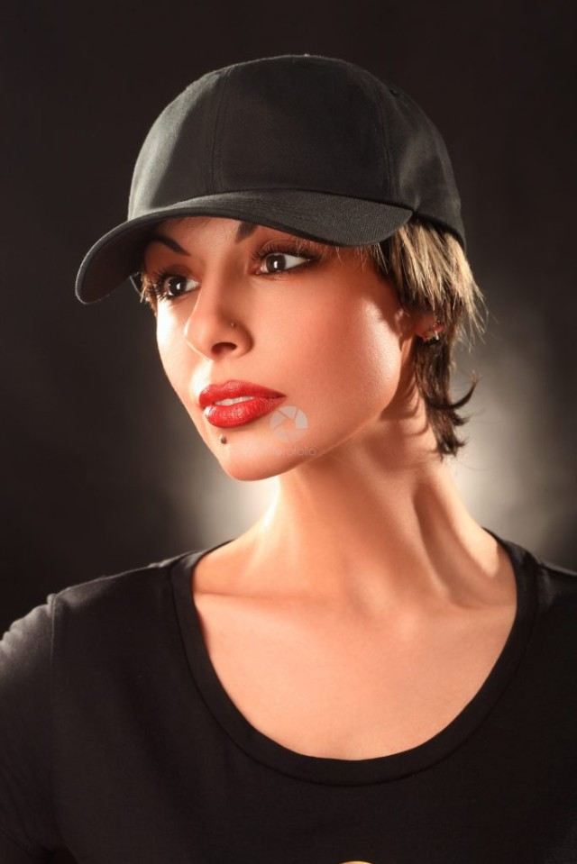 Studio portrait of a pretty short hair girl wearing a black cap