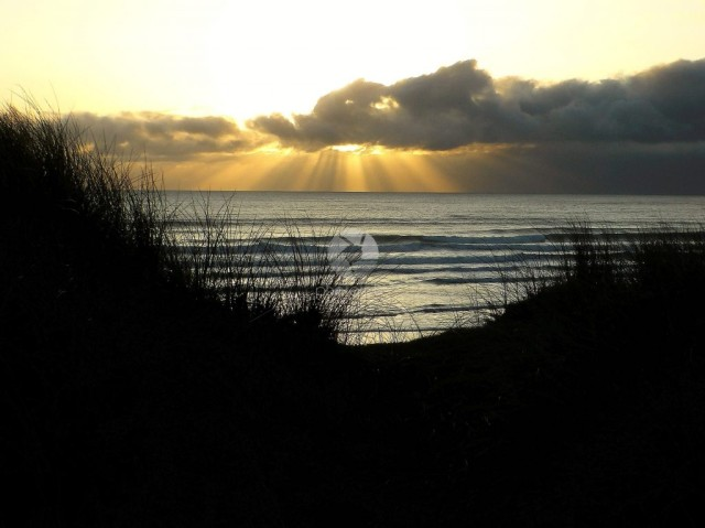 Freshwater West in Pembrokeshire at sunset through the sand dunes