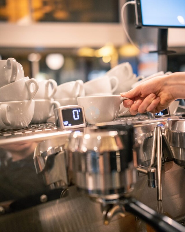 Coffee Cup Being Lifted From Top of Espresso Coffee Machine