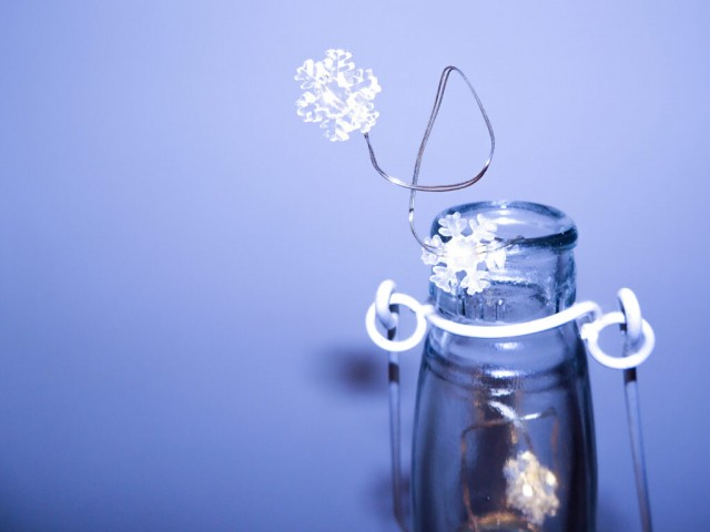 White Snowflake lights in glass bottle with blue background
