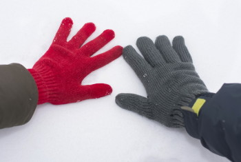 male and female hand in gloves touching snow