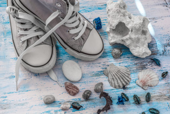 Travel stll life with sneakers and stones on wooden board