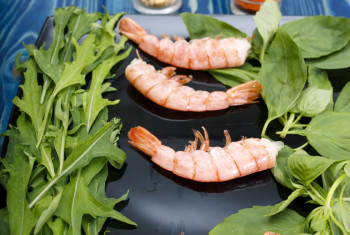 Shrimps on a black plate – the ingredients for the salad