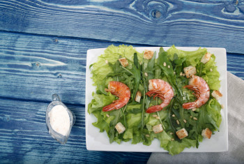 Salad with shrimps on a blue table