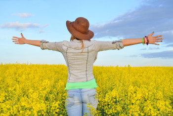 Girl embracing a field of yellow flowers