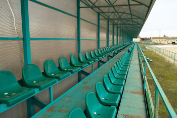 Rows of seats in an empty stadium. Green seats at the stadium