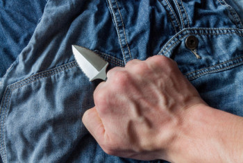 Neck knife on jeans background in hand.