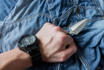 Serrated knife on jeans background in left hand.