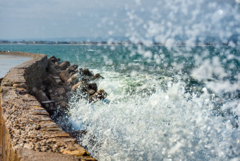 A wave, sea foam and breakwater