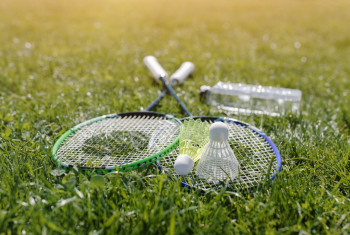 Two badminton rackets and a bottle of water shot at sunset