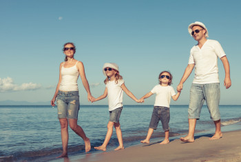 Happy family standing on the beach at the day time.