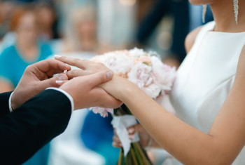 A groom puts a wedding ring on the bride's finger