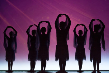 Silhouette of young cute girls dancing in front of a purple back