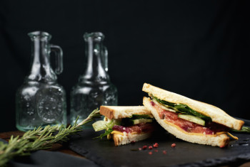 Sandwich with fish, herbs and cheese on a dark background.