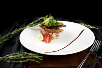 Salad with grilled beef and baked chicken on a dark background.