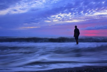 Man standing in ocean waves at sunset, cloudy sky.