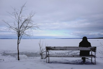 Rear view of a person sitting on a bench in winter, looking over a snow covered, frozen lake.