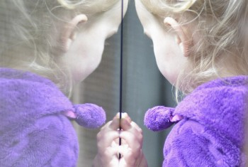 Mirror image of a young blond girl with pigtails standing at a window.
