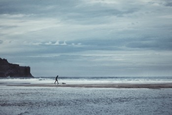 Person on a sandy beach by the ocean under a cloudy sky.