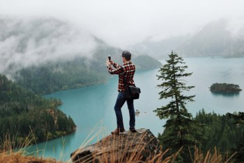 Man standing on a rock above a lake, taking a picture with his smart phone.