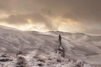Man standing on a rock in a mountainous landscape in winter.