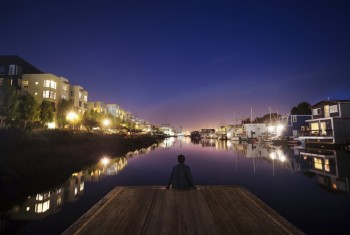 Evening scene, man sitting on a wooden jetty on a river, illuminated houses lining the riverbank.