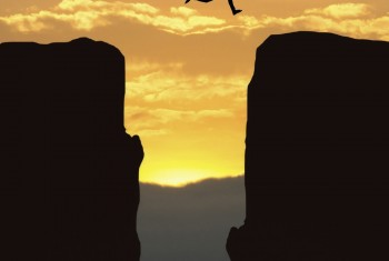 Man leaping across a chasm between two rocks at sunset.
