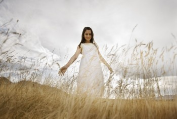 A girl in a white dress in long grass, looking down with her arms held out by her side.