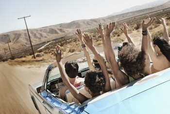 A group of friends in a pale blue convertible on the open road, driving across a dry flat plain surrounded by mountains.