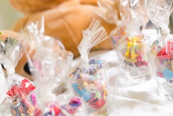 Glasses of Bagged Sweets on White Table with Teddy Bears in Back