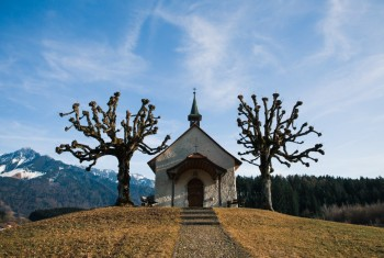 Small Swiss Chapel in Winter with Mountains in the Background