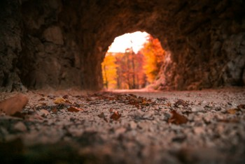 Stone Carved Tunnel and Red Sunset Light opening on Autumn Folia